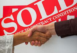 Man and woman shaking hands in front of SOLD sign