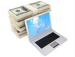 Laptop with money behind it