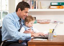 Businessman holding baby while working on laptop at home